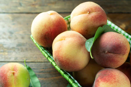 Ripe peaches in basket on wooden background. Home harvest from your own garden. Healthy eating. Reklamní fotografie