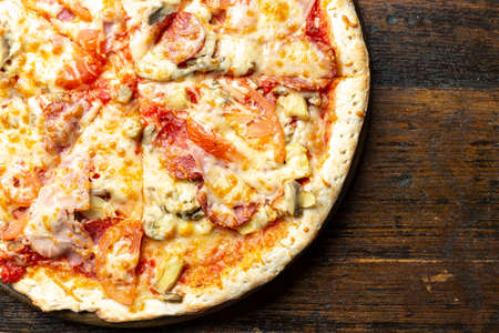 Fresh italian pizza with bacon, tomatoes, mushrooms and cheese on a wooden background. Italian food. Space for text. Top view.