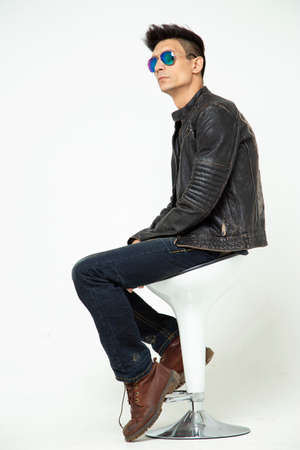 Stylish young man wearing glasses on a white background sitting on a chair in the studio