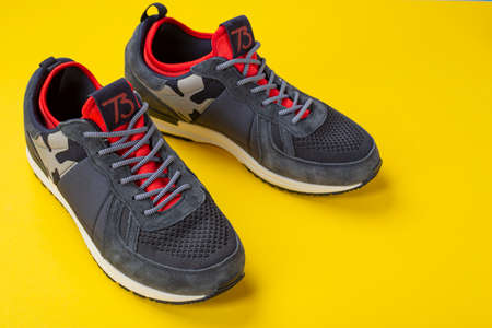 Insulated sneakers on a yellow background. Warm shoes concept. Space for text.
