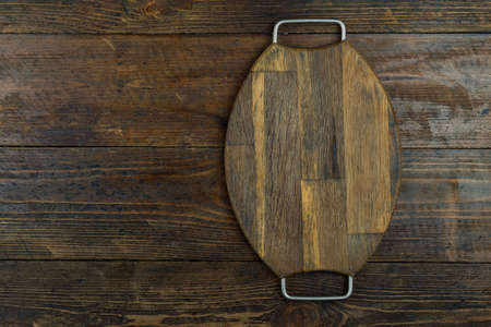 Cutting board or kitchen board on a wooden background. Space for text. Top view.
