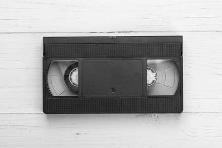 VHS tape from the 80s and 90s on white wood background. Retro media aesthetic, magnetic videotape movie storage concept studio shot