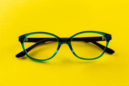 Stylish glasses for correcting vision on a yellow background. Fashionable accessory. Top view.