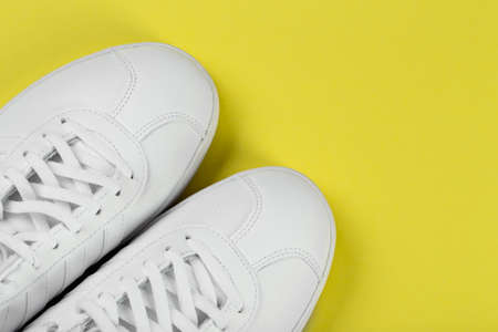 Women's stylish sneakers on a yellow background. Lifestyle sneaker sport shoe. Space for text. Top view.