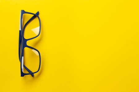 Fashionable glasses in blue frames for vision on a yellow background. Health concept. The medical field that studies the eyes. Reklamní fotografie