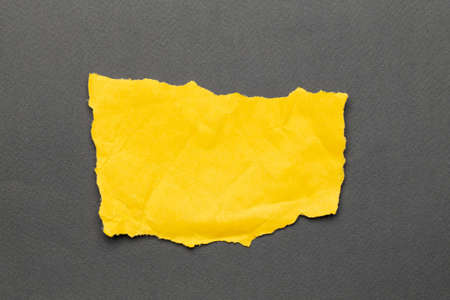 Torn real paper yellow color scraps on gray background. Top view Reklamní fotografie