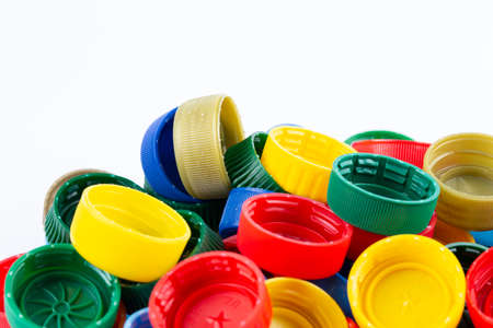 Group of multi colored bottle caps on white background.