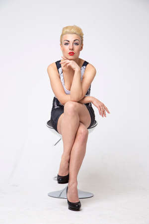 sexy blonde woman sitting on a chair in the studio on a white background