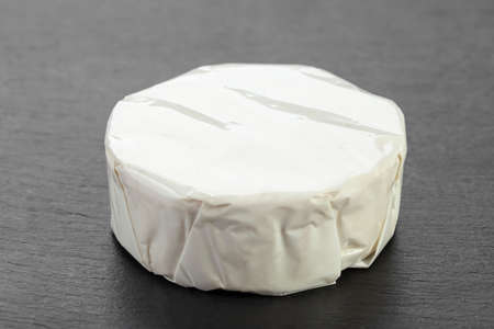 Cheese Camembert on a black board for serving food. French gastronomy traditions.