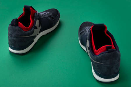 A pair of men's insulated sneakers close-up on a green background.