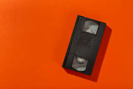 Videotape without a cover on an orange background. Top view. Reklamní fotografie