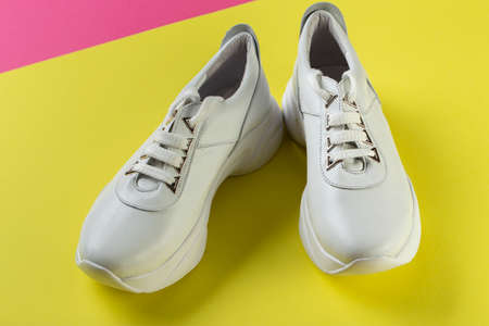 Women's stylish sneakers on a yellow pink background. Lifestyle sneaker sport shoe. Space for text. Top view.