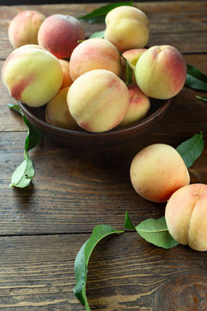 Fresh harvest of peaches in a clay bowl on a wooden rustic table. Peach leaves are present in the composition. Organic fruit, vegan food.