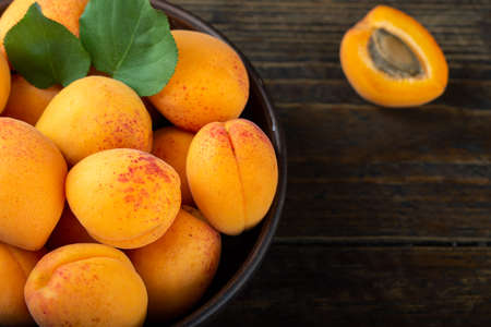 Ripe apricots and apricot leaves in a bowl on a wooden table. Fresh fruits from the home garden. Healthy food.