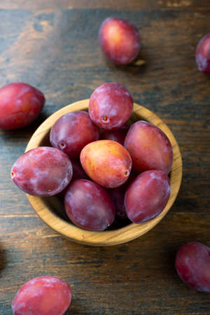Ripe plums in a wooden bowl on the table. Harvesting season.
