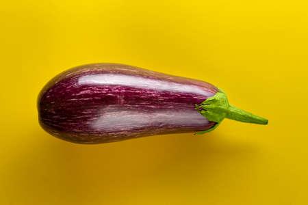 Raw purple eggplant on a yellow background. Fresh vegetables.