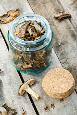 dried mushrooms in a jar and on a wooden table