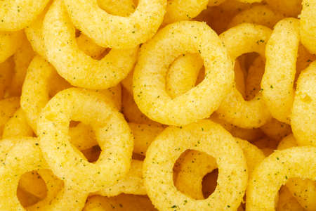 Beer snacks. Background of corn rings of sticks with cheese and green onion flavor. Junk food.