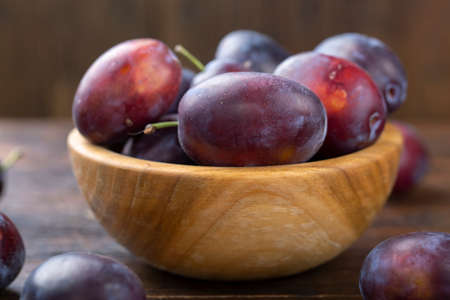 Fresh plums in a wooden bowl on a brown table. Gathering the summer harvest. 写真素材