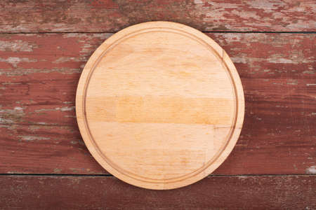 Cutting board for cutting bread, pizza or steak on a wooden background. Top view.