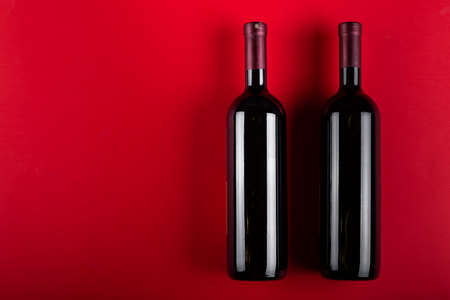 Two bottles of red wine on a red background. Romantic mood. Space for text. Top view.