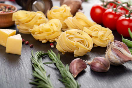 Raw pasta tagliatelle with fresh tomatoes, peppers, mushrooms, asparagus beans, spices and cheese on black table. Food ingredients for Italian spaghetti.