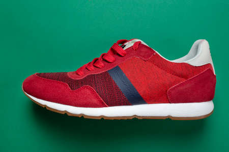 New red sneakers on a green background. Casual shoes. Space for text. Top view.