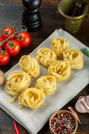 Raw pasta tagliatelle with fresh tomatoes, peppers, asparagus beans, spices and cheese on wood background. Food ingredients for Italian spaghetti.