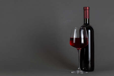 Red wine bottle and glass on a gray background. Wine drinking culture concept. Space for text. 写真素材