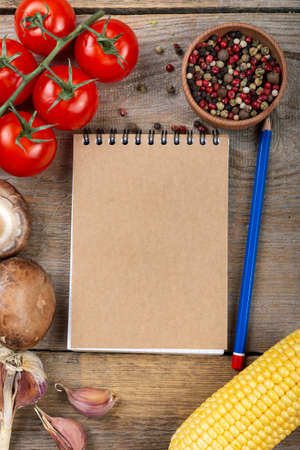 Notepad and pencil with vegetables on a wooden background. Space for text. Top view.