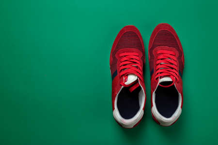 Pair of new red sneakers on a green background. Casual shoes. Space for text. Top view.