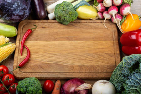 Exposition of fresh organic vegetables on a wooden table with space for text in the center. Healthy food -diet concept. Top view. 写真素材