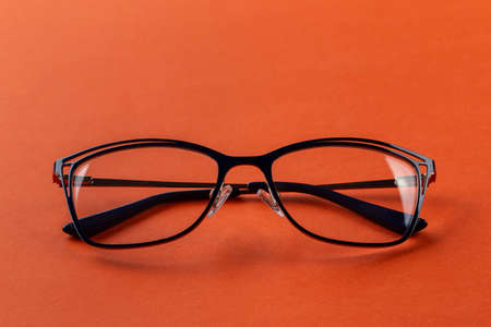 Glasses for vision in black frames on an orange background. Fashion accessories.