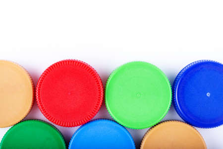A lot of plastic bottle caps on a white background. Recycling collection and processing plastic bottle caps. Cap material is recyclable. Space for text.