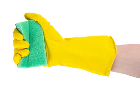 Cleaning concept - hand in a yellow rubber glove holds a green sponge isolated on white background. 写真素材