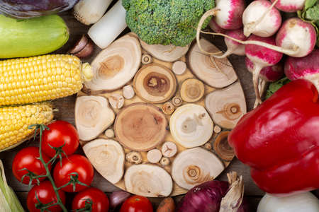 A vegetable background in the center of which is an empty cutting board. Healthy eating. Harvesting concept. Space for text. Top view. 写真素材
