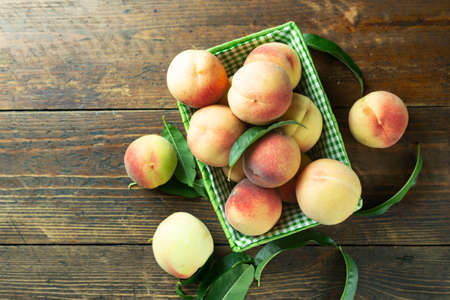 Fresh harvest of peaches in a basket on a wooden rustic table. Peach leaves are present in the composition. Organic fruit, vegan food.