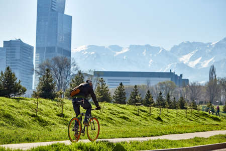 A cyclist rides on a road in the city against a background of green grass and mountains. city of Almaty. Ecological transport.