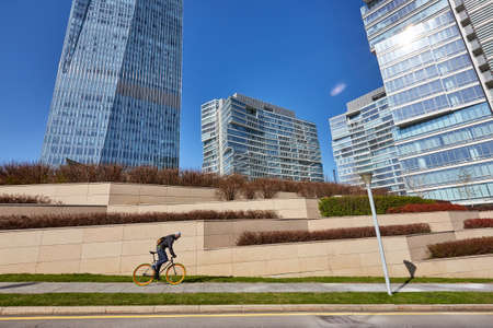 A man is riding a bicycle against the background of high-rise buildings. sunny day