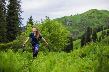 Delighted girl walks barefoot on the grass. Young girl with dreadlocks walking in the forest she took off her shoes. Summer mood Stock fotó