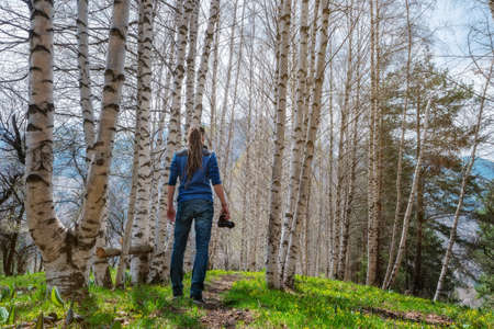 A man photographer stands on the trail in the spring birch forest. The guy holds a camera in his hand. View from the back. Mountain landscape. Spring in the fresh air. Fresh young grass and wildflowers. Alma-Ata's region. Kazakhstan.