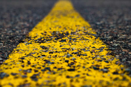 Road marking line with yellow paint on asphalt. Marking the motorway. Close-up