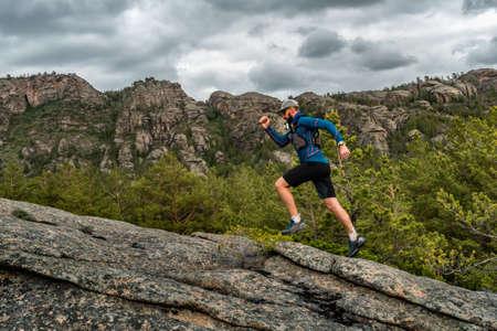 Mężczyzna biegacz na szlaku górskim. Sportowiec biega w górach wśród skał. Mężczyzna w niebieskiej koszulce i czarnych spodenkach trenuje na świeżym powietrzu