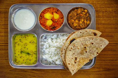 Thali - Traditional Indian Food. Steel tray with multiple compartments for rice, dal, vegetables, roti, papad, dahi, small amounts of chutney or pickle, and a sweet dish.