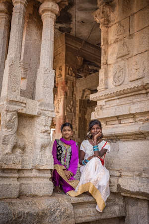 Hampi, Karnataka, INDIA - JANUARY 16, 2018: Portrait of Indian girls dressed in national dresses. Girls are sitting at the entrance to the ancient temple. Group of Monuments at Hampi 新聞圖片