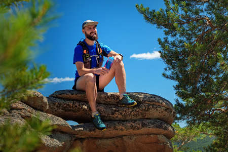 A male runner is sitting on the edge of a cliff, he is resting after a successful workout. Outdoor trail running. Man in blue t-shirt and black shorts