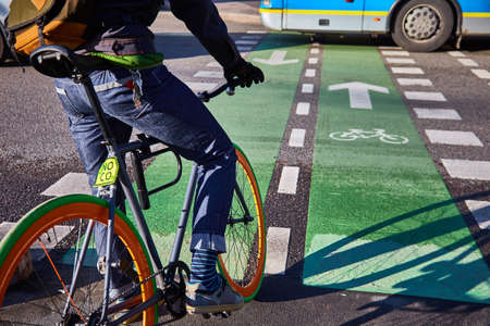 A cyclist in the city goes on a pedestrian crossing. Eco-friendly mode of transport. Bicycle with fixed speed