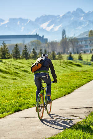 Un ciclista cabalga por una carretera de la ciudad con un fondo de hierba verde y montañas. ciudad de Almaty. Transporte ecológico.