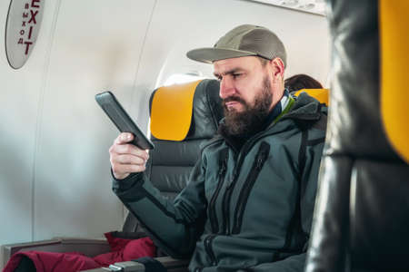 A male traveler is reading an e-book while flying on an airplane. Pastime during the flight on the Airbus