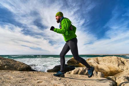 Athlete guy runs along the seashore on a sunny day. Trail Running. Mangystau Peninsula. Kazakhstan